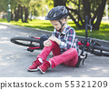 Crying girl is sitting next to her bike 55321209