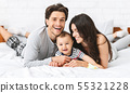 Cheerful baby lying on bed with parents 55321228