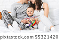Sweet little baby smiling, sitting on bed with loving parents 55321420
