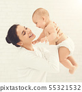 Young mom holding her happy baby in air 55321532