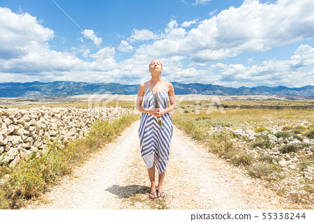 Caucasian young woman in summer dress holding bouquet of lavender flowers enjoying pure 55338244