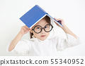 Happy little Asian girl holding book over head 55340952