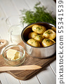 Young potatoes boiled in  pot with dill and butter on wooden board 55341539