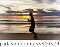 Unidentified man running on the beach at sunset. 55346529