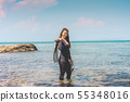 woman wearing wetsuit and holding Diving equipment 55348016