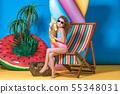 Girl in swimwear and sunglasses sitting in rainbow deck chair 55348031