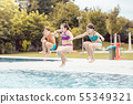 Friends holding hand jumping in swimming pool 55349321