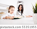 Mother sitting with baby girl and teaching her to read. 55351955