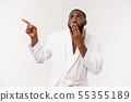 Black guy wearing a bathrobe pointing finger with surprise and happy emotion. Isolated over whtie 55355189