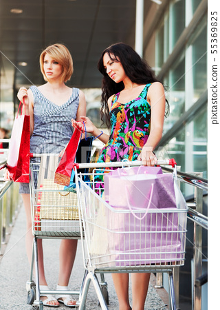 Two young women with shopping carts 55369825
