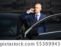 Young businessman calling on the phone at the car 55369943