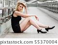 Sad young woman sitting on the sidewalk 55370004