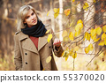 Happy blond woman in autumn forest 55370020