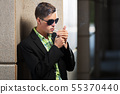 Young man in sunglasses smoking a cigarette 55370440