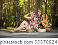 Two hippie girls with guitar in a summer forest 55370924