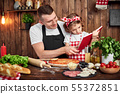 Father and daughter reading recipes book while cooking pizza 55372851