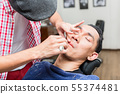 Professional barber shaving with razor 55374481