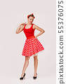 smiling pin up woman in polka dot red dress 55376075