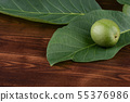 green walnut on a sheet, on a wooden background 55376986