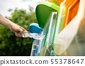 Close up hand putting plastic bottle into bin. 55378647