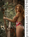 Attractive red woman with python. Beautiful ginger girl observe for snake in tropical garden 55379746