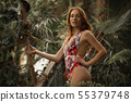 Attractive red woman with python. Beautiful ginger girl observe for snake in tropical garden 55379748