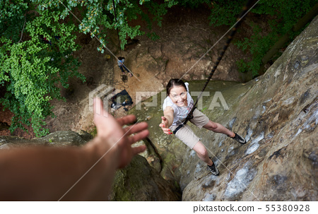 Happy woman climbing rock. Carefree hiker smiling her friend. Man helping his friend to climb rock. 55380928
