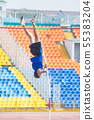 Pole vault - a bearded athletic man rest against the ground on the pole and ready to jump over 55383204