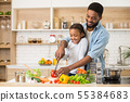 Dad teaching his daughter to cook salad 55384683