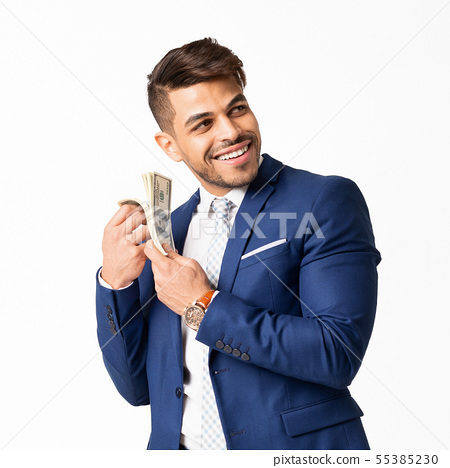 Happy business man listening to bundle of notes sounds 55385230