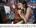 girl tourist playing slot machine in casino 55391176