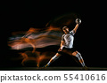 Young handball player against dark studio background in mixed light 55410616