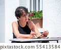 portrait of mature woman reading magazine in the 55413584