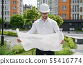 Engineer in hardhat holding architectural project on paper. 55416774
