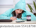 teenager girl with a hood doing her homework 55418798