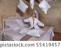 Cheerful woman throwing up pillows on bed 55419457