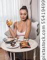 Woman having tasty breakfast in hotel 55419499