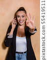 Cheerful entrepreneur showing OK gesture during 55419511