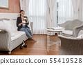 Businesswoman drinking hot beverage in hotel room 55419528
