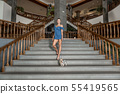 Smiling woman with dog posing on steps 55419565