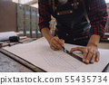 Carpenter working with equipment on wooden table 55435734