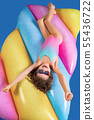 Beautiful little girl in colorful swimsuit and sunglasses lies , relax on an air mattress 55436722