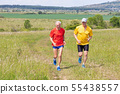 Senior runner running with his adult son on meadow 55438557