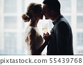 Bride and groom embracing and holding by hands 55439768