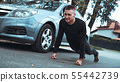 Handsome man near the car. The athlete wrung out next to the machine 55442739