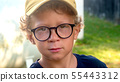 portrait of a little blond boy with glasses 55443312