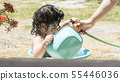 Little young girl playing with water hose and 55446036