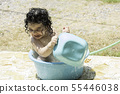 Happy little young girl has fun playing with hose 55446038