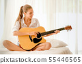 Beautiful girl with white shirt play guitar on bed 55446565