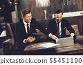 Young man smiling and pointing to the laptop of his colleague 55451190